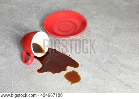Cup With Saucer And Coffee Spill On Grey Table. Space For Text