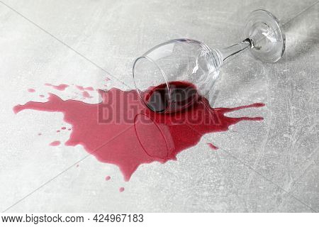 Overturned Glass With Red Wine Spill On Grey Table