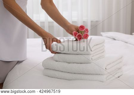 Chambermaid Putting Flowers With Fresh Towels In Hotel Room, Closeup