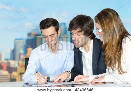 Successful Young Office Team Discussing Over A Document.