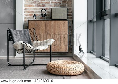 Cozy Lounge Zone Near Panoramic Window With Metal Chair, Straw Ottoman And Modern Equipment For List