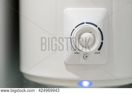 Close Up Of White Electric Boiler Temperature Control Knob With Blue Light Indicator, Modern Water H