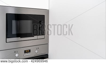 Close Up Of Steel Modern Microwave With Control Knobs And Panel To Display Time In White Kitchen Int