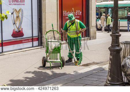 Paris, France - June 9, 2015: Street Cleaner Sweeps The Floor At The Sidewalk In Paris, France.