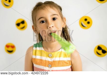 A Girl Blows A Festive Pipe On A White Background With A Variety Of Emoticons. World Emoji Day. Anth