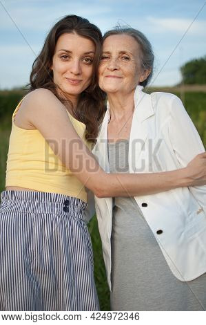 Senior Mother With Gray Hair With Her Adult Daughter Looking At The Camera In The Garden And Hugging