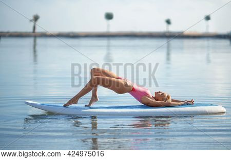 Beautiful Fitness Girl With A Perfect Butt And Body Posing Outdoor On The Surfboard In The Rays Of S