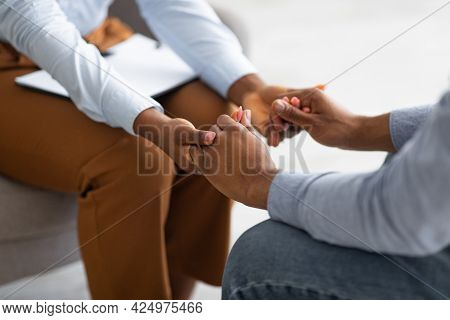Professional Compassion. Psychotherapist Supporting Her Depressed Male Patient, Holding His Hand Ind