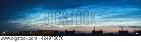 Wide Panorama Of The Night Sky And Spectacular Silvery Clouds, Silhouettes Of City Buildings Against
