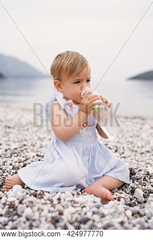 Little Girl Sits On A Pebble Beach And Drinks Water From A Bottle