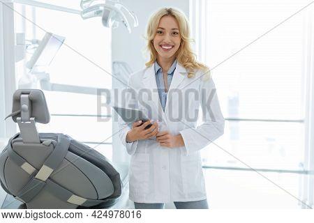 Female Dentist Smiling And Holding Digital Tablet In Dental Cabinet