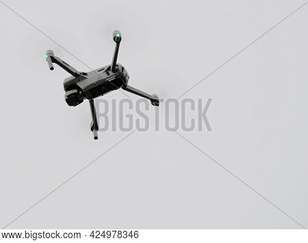Image of a drone flying against the sky with rainy clouds