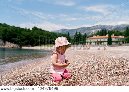 Little Girl Sitting On Her Knees On The Beach By The Water. Villa Milocer