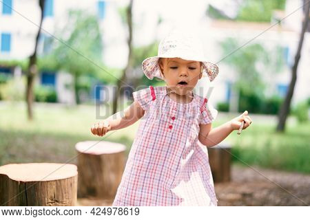 Little Girl Stands By The Stumps In The Yard With A Twig In Her Hand