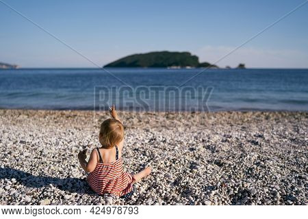 Little Girl In A Dress Sits On A Pebble Beach And Shows Her Finger To The Sea. Back View