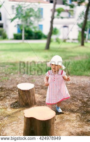 Little Girl In A Hat Walks Among The Stumps In The Yard