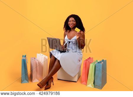 Full Length Of Millennial Black Woman With Laptop And Credit Card Shopping Online, Surrounded By Bri