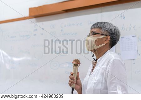 Professor Senior Asian Teaching Explain Wear Medical Face Mask For Safety Speaking Microphone At Whi