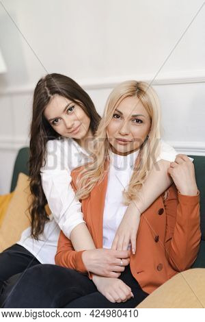 Beautiful Mother And Adult Daughter Hugging Portrait Close Up, Sitting On Couch At Home, Smiling Wom