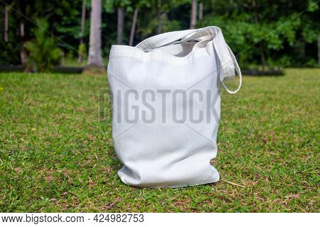 Canvas Tote Bag On Sunny Green Lawn. Simple Tote Bag Mockup. Summer Landscape With Green Lawn And Fo
