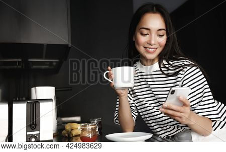 Morning Breakfast. Young Asian Woman Eating And Drinking Coffee In Kitchen While Looking At Smartpho