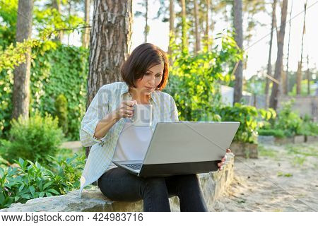 Beautiful Emotional Middle Aged Woman Relaxing In Garden With Cup Of Tea And Laptop