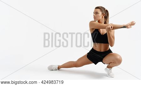 Dynamic Movement. Determined Young Sportswoman In Sport Clothing, Stretching Legs And Arms, Body War