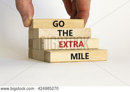 Go The Extra Mile Symbol. Wooden Blocks With Words 'go The Extra Mile'. Businessman Hand. Beautiful