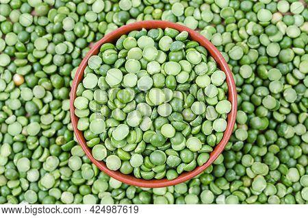 Green Split Peas In Cup On Split Peas Background.