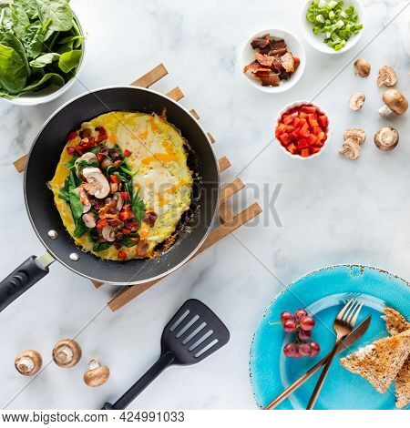 Top Down View Of Ingredients Used To Make A Breakfast Omelette With The Omelette Being Made In The F