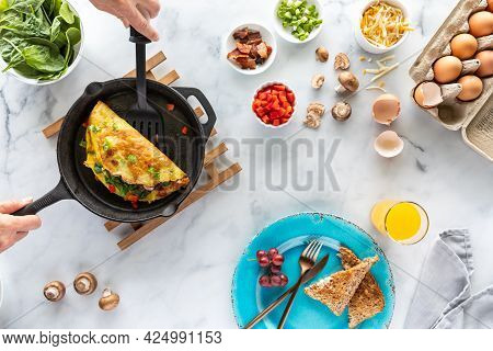 Top Down View Of Hands Holding A Spatula Serving Up A Freshly Made Omelette, Beside Ingredients Used
