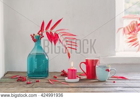 Red Autumn Leaves In Glass Vase And Viburnum Berries  And Cup Of Tea  On Wooden Table