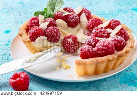 Cut Mini Tartlet With Vanilla Custard, Raspberries, Almond Flakes And A Sprig Of Mint Close-up.