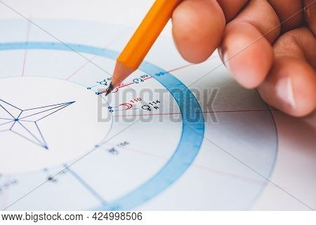 Modern Astrologer's Desktop. Hand With A Pencil. Astrological Charts And Tables With The Coordinates