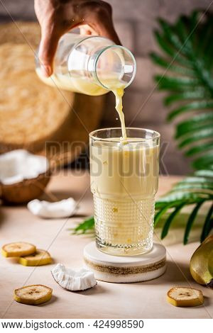 Woman Hand Pouring Banana Cocktail With Coconut Milk In A Glass On Light Beige Background With Palm
