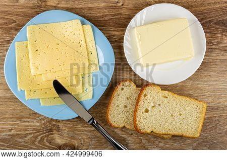 Few Thin Slices Of Cheese In Light-blue Glass Plate, Table Knife, Piece Of Butter In White Plate, Sl