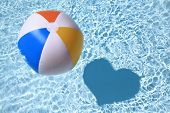 Summer love, Beach Ball on the swimming Pool with heart shaped shadow