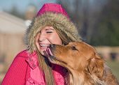 Dog Kissing Teenage Girl in Winter Clothes poster