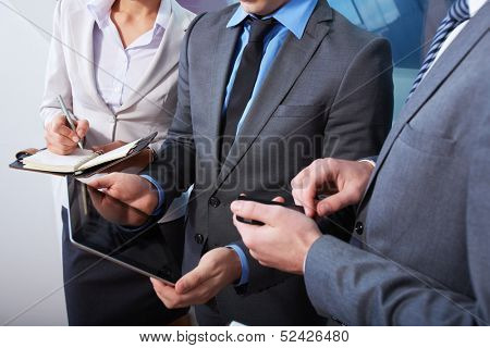 Image of young businessman with touchpad showing somwthing to his coleagues at meeting