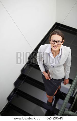 Above angle of smart businesswoman looking at camera while descending staircase