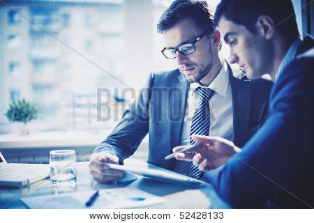 Image of two young businessmen discussing project at meeting