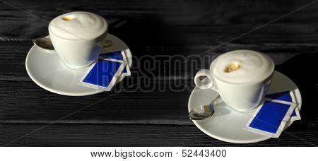 two cups of coffee on a black wooden table
