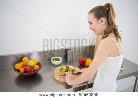 Pretty young woman preparing vegetables in the kitchen at home