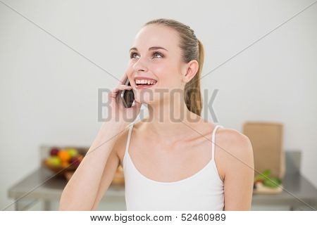 Happy young woman talking on smartphone in the kitchen at home