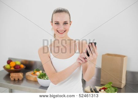 Happy young woman sending a texting in the kitchen at home