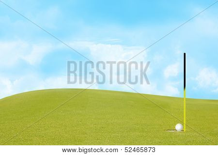 golf on green Include slope and sky.