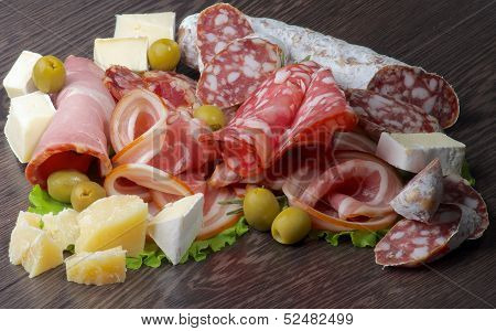 Arrangement of Delicatessen Cold Cuts with Smoked Ham Pepperoni Salami Finocchiona Green Olives Grana Padano and Camembert Cheese closeup on Dark Wooden background poster