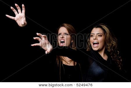 Portrait Of Shouting Young Women Showing Hand Gesture