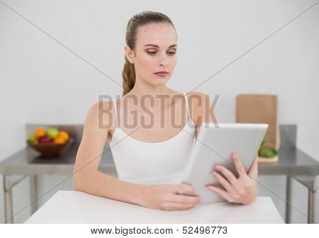 Serious young woman using her tablet pc in the kitchen at home