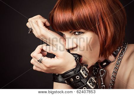 sexy fashionable woman gnaws leather handcuffs